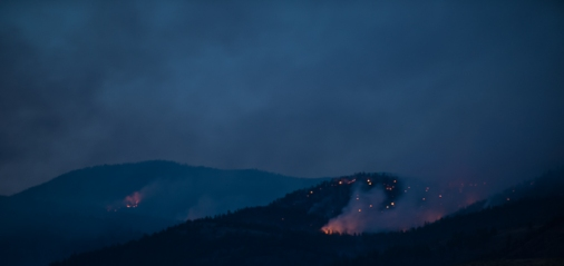 As darkness settles in, the smoke lifts and flames become visible