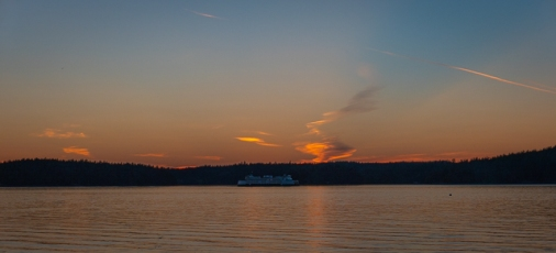 A ferry passes at sunset