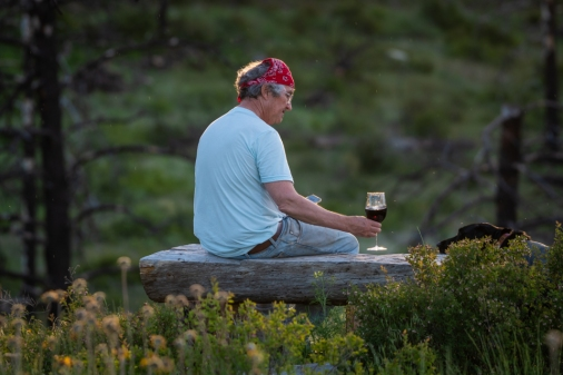 Ken enjoys a glass of wine while watching the sunset after hauling rock for our garden border.